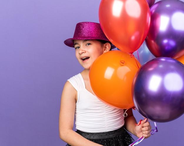 Fröhliches junges kaukasisches mädchen mit violettem partyhut, der heliumballons isoliert auf lila wand mit kopienraum hält