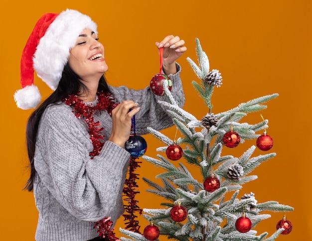 Fröhliches junges kaukasisches mädchen mit weihnachtsmütze und lametta-girlande um den hals, das in der profilansicht in der nähe des weihnachtsbaums steht und ihn mit weihnachtskugeln schmückt, die isoliert auf oranger wand lachen