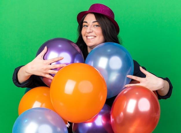 Fröhliches junges kaukasisches partymädchen mit partyhut, das hinter ballons steht und sie isoliert auf grüner wand umarmt