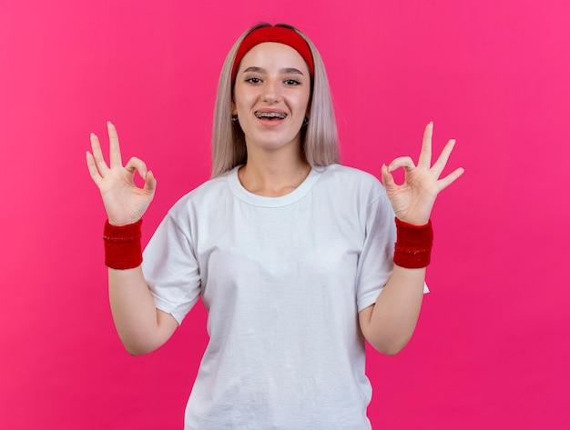 Fröhliches junges kaukasisches sportliches mädchen mit hosenträgern, das stirnband und armbänder trägt, gesten ok handzeichen mit zwei händen two