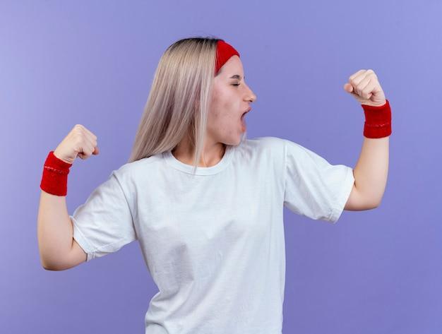 Fröhliches junges kaukasisches sportliches mädchen mit hosenträgern, das stirnband und armbänder trägt, spannt den bizeps an
