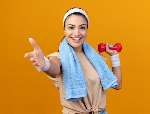 Fröhliches junges, kaukasisches, sportliches mädchen mit stirnband und armbändern, das die hantel anhebt und die hand in richtung kamera ausstreckt, mit handtuch um den hals isoliert auf oranger wand orange