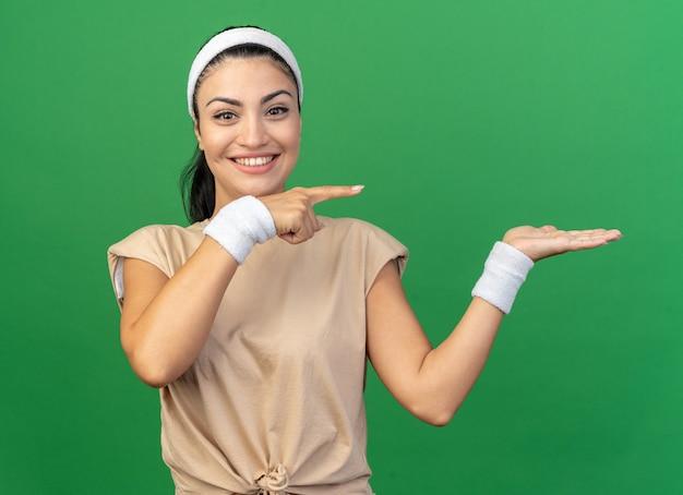Fröhliches junges kaukasisches sportliches mädchen mit stirnband und armbändern, das leere hand zeigt, die auf die seite zeigt, isoliert auf grüner wand