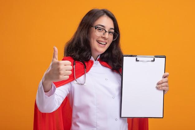 Fröhliches junges kaukasisches superheldenmädchen in rotem umhang mit arztuniform und stethoskop mit brille, die zwischenablage zur kamera zeigt, die daumen nach oben zeigt