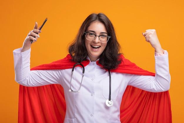 Fröhliches junges kaukasisches superheldenmädchen mit arztuniform und stethoskop mit brille, das mobiltelefon hält, die ja-geste isoliert an der wand macht
