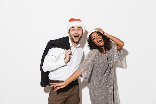 Fröhliches junges klug gekleidetes paar, das neujahr feiert, isoliert über weißem raum