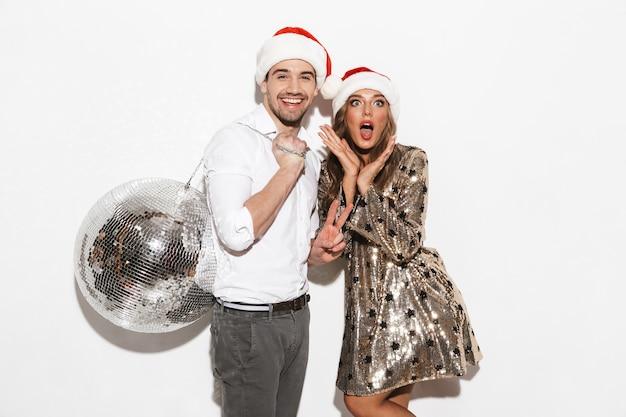 Fröhliches junges klug gekleidetes paar, das neujahrsparty lokalisiert über weißem raum feiert