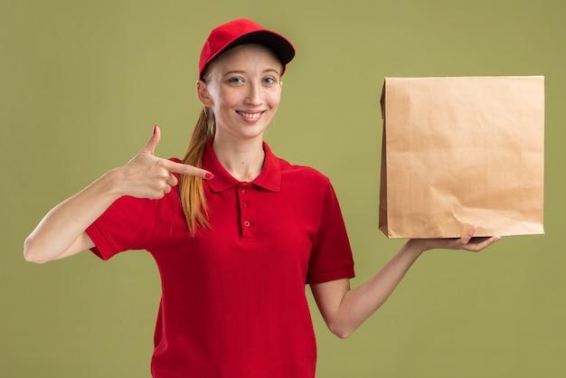 Fröhliches junges liefermädchen in roter uniform und mütze, das das paket hält und mit dem zeigefinger darauf zeigt, lächelt selbstbewusst