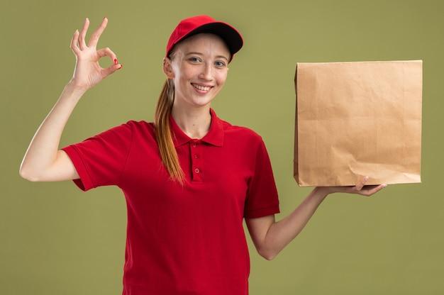 Fröhliches junges liefermädchen in roter uniform und mütze, das paket hält, das zuversichtlich lächelt und dabei ein gutes zeichen macht