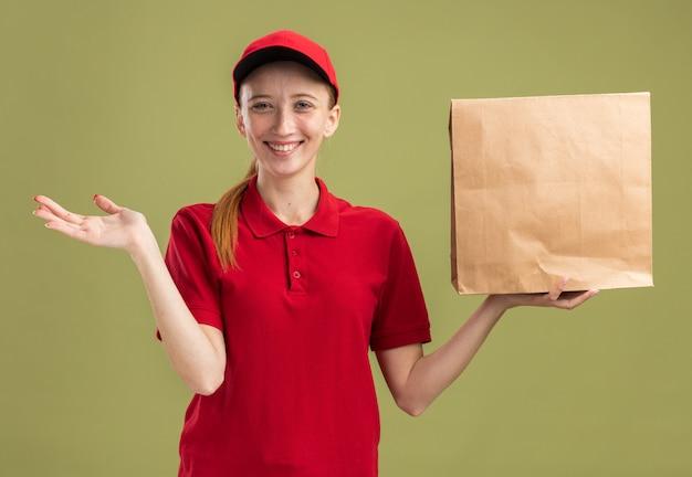 Fröhliches junges liefermädchen in roter uniform und mütze mit paket, das selbstbewusst mit ausgestrecktem arm lächelt