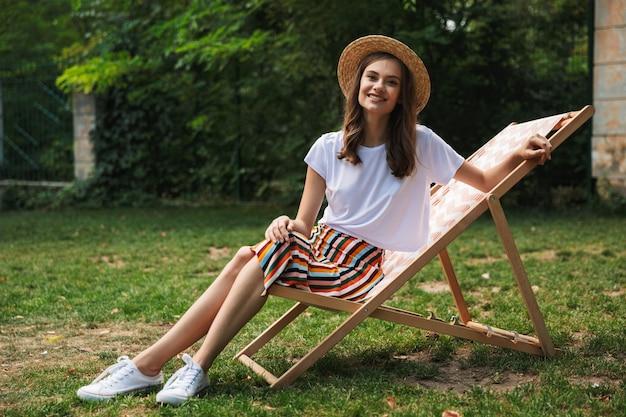 Fröhliches junges mädchen, das auf einer hängematte am stadtpark draußen im sommer ruht