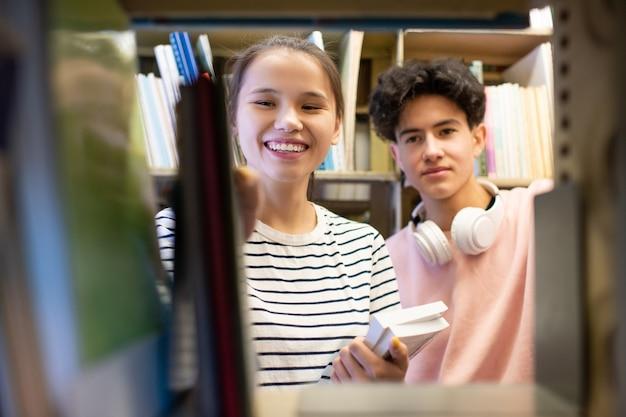 Fröhliches junges mädchen, das buch vom bücherregal in der universitätsbibliothek nimmt, während sie ihrem klassenkameraden bei der wahl hilft