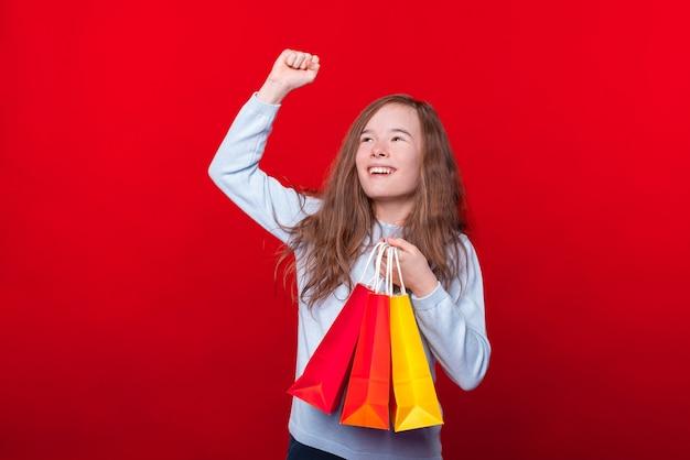 Fröhliches junges mädchen, das bunte einkaufstaschen hält und feiert
