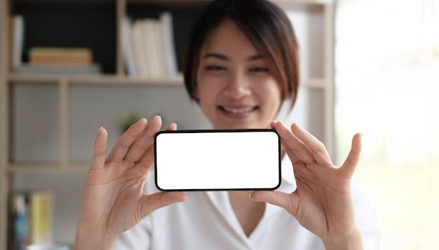 Fröhliches junges mädchen, das smartphone auf hand mit einem leeren bildschirm hält.