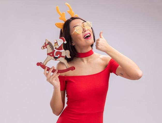 Fröhliches junges mädchen mit rentiergeweih-stirnband und brille, das den weihnachtsmann auf einer schaukelpferdfigur hält, die daumen mit geschlossenen augen isoliert auf weißem hintergrund zeigt