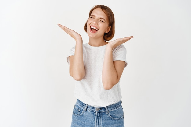 Fröhliches junges, natürliches mädchen, das lacht und ein schönes gesicht ohne make-up zeigt, die hände in der nähe des kopfes hält und sorglos lächelt, weiße wand