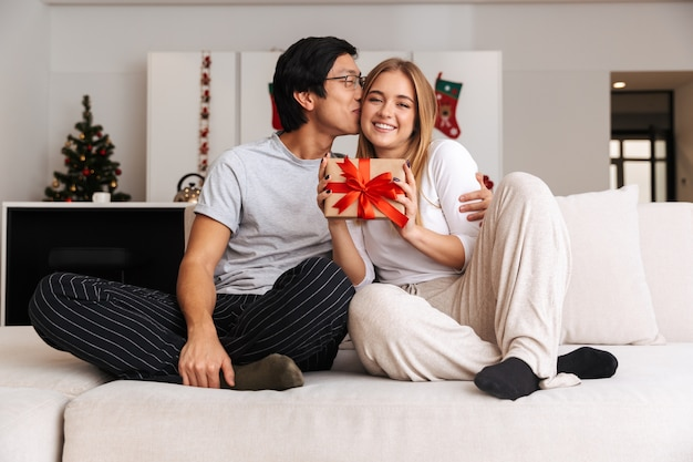 Fröhliches junges paar, auf einer couch zu hause sitzend, geschenkbox zeigend, küssend