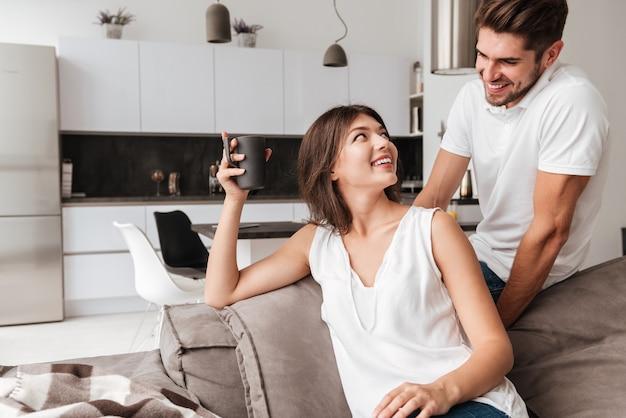Fröhliches junges paar, das auf sofa sitzt und kaffee zu hause trinkt