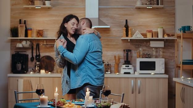 Fröhliches junges paar, das beim romantischen abendessen tanzt und küsst. glücklich verliebtes paar, das zu hause zusammen isst, das essen genießt und ihr jubiläum feiert.
