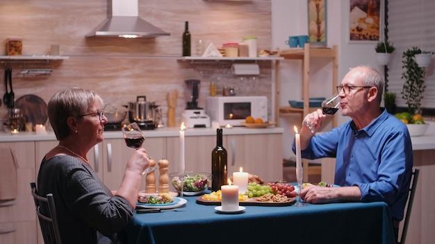 Fröhliches junges paar, das ein romantisches abendessen mit rotwein genießt. ältere alte leute klirren, sitzen am tisch in der küche, genießen das essen, feiern ihr jubiläum im esszimmer.