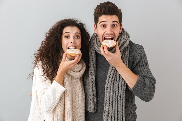 Fröhliches junges paar, das pullover und schals trägt, die isoliert über grauer wand stehen und donuts zeigen