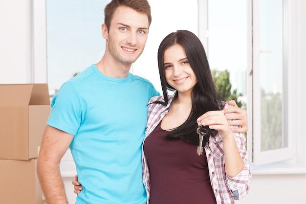 Fröhliches junges paar, das schlüssel hält und lächelt, während es in ihrem neuen haus steht