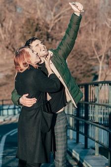 Fröhliches junges paar, das selfie auf der brücke macht. zwei glückliche menschen liebesgeschichte auf der straße