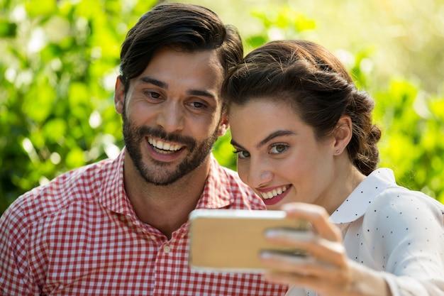 Fröhliches junges paar, das slefie durch smartphone am park nimmt
