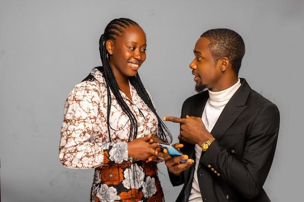 Fröhliches junges paar, das smartphone anschaut