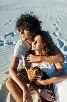 Fröhliches junges paar, das spaß am strand mit ihrer bengalkatze hat.