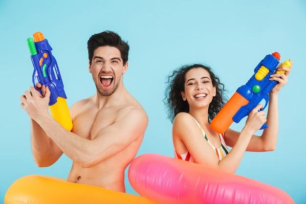 Fröhliches junges paar, das spaß am strand trägt, isoliert aufblasbare ringe trägt und mit wasserpistolen spielt