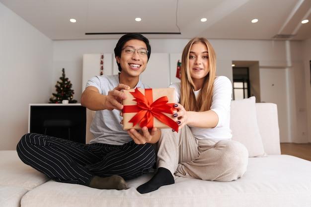 Fröhliches junges paar, das zu hause auf einer couch sitzt und geschenkbox zeigt
