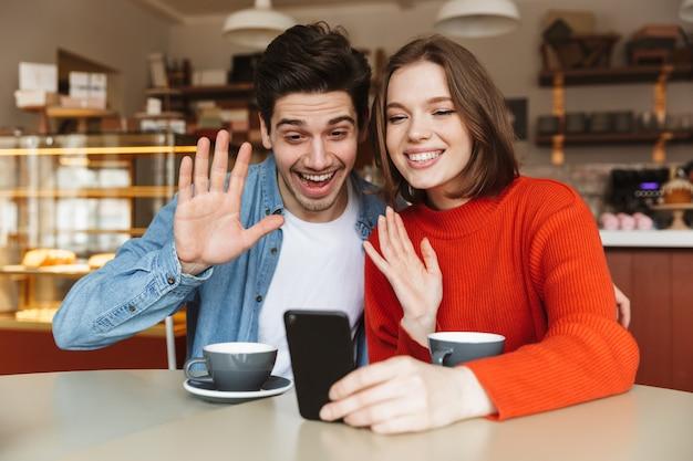 Fröhliches junges paar, das zusammen an einem kaffeetisch sitzt