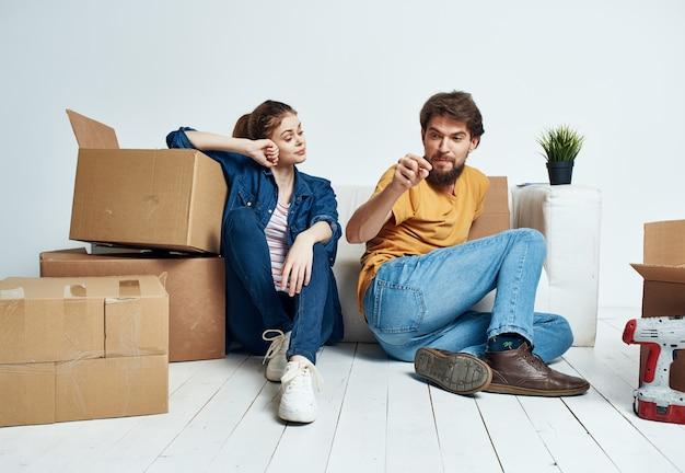 Fröhliches junges paar im zimmer auf der couch mit kisten