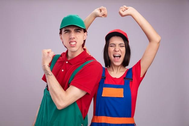 Fröhliches junges paar in bauarbeiteruniform und mütze, das ja geste macht, das kameramädchen ansieht, das die hände mit geschlossenen augen einzeln auf weißer wand hebt
