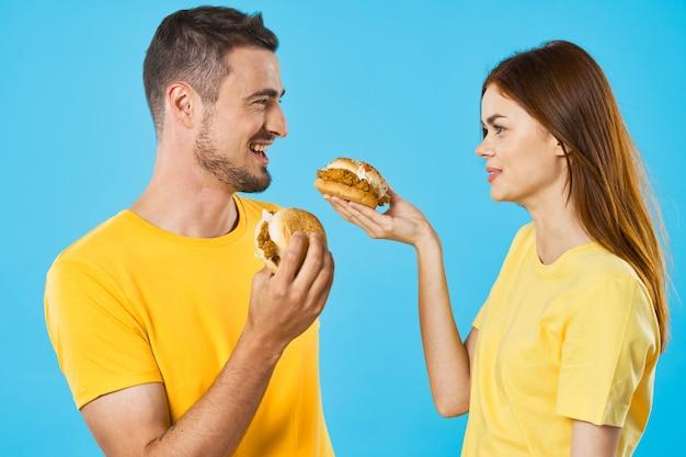 Fröhliches junges paar in gelben t-shirts mit hamburgern