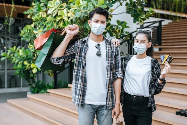 Fröhliches junges paar in maske mit mehreren papiereinkaufstüten