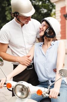 Fröhliches junges paar in sturzhelmen, die zusammen mit roller draußen aufwerfen