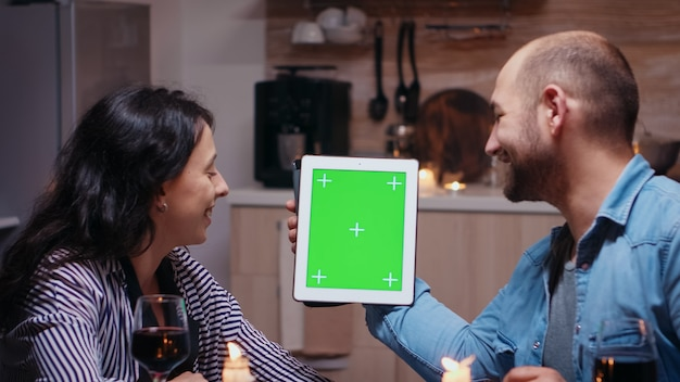 Fröhliches junges paar mit grünem mock-up-bildschirm digitalen isolierten tablet-computer. mann und frau betrachten die chroma-key-anzeige der greenscreen-vorlage, die während des abendessens am tisch in der küche sitzt.
