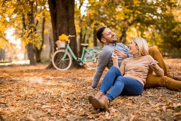 Fröhliches junges paar sitzt auf dem boden im herbstpark