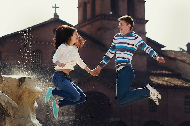 Fröhliches junges paar springt vor dem brunnen irgendwo in rom