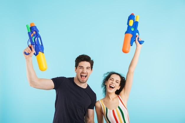 Fröhliches junges paar steht isoliert und hat spaß mit wasserpistolen