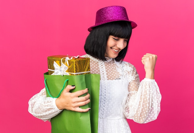 Fröhliches junges partymädchen mit partyhut, das geschenkpaket in papiertüte hält und nach unten schaut und die ja-geste isoliert auf rosa wand macht