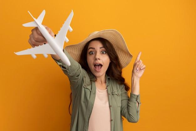 Fröhliches junges schönes mädchen mit olivgrünem t-shirt und hut, das spielzeugflugzeug an kamerapunkten an der seite isoliert auf gelber wand mit kopierraum hält