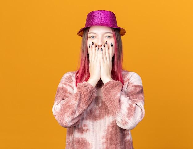 Fröhliches junges schönes mädchen mit partyhut bedecktes gesicht mit den händen isoliert auf oranger wand