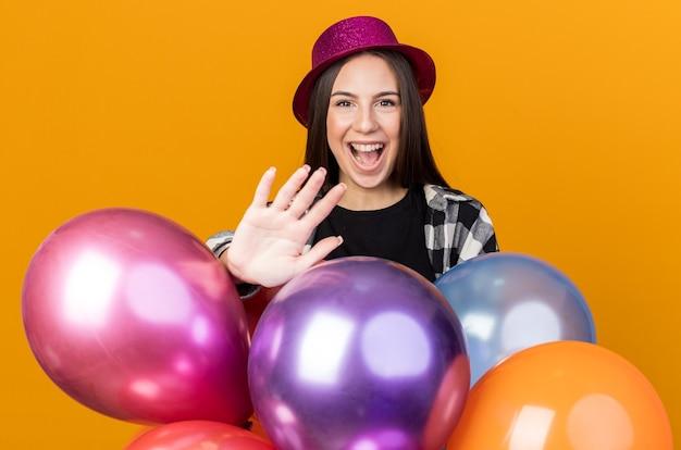 Fröhliches junges schönes mädchen mit partyhut, das hinter luftballons steht und die hand isoliert auf oranger wand hält