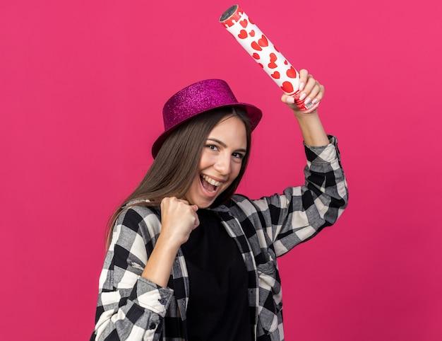 Fröhliches junges schönes mädchen mit partyhut, das konfettikanonen hält und ja-geste zeigt