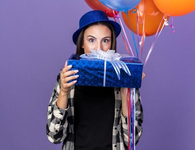 Fröhliches junges schönes mädchen mit partyhut mit ballons bedecktes gesicht mit geschenkbox