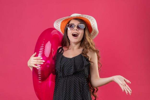 Fröhliches junges schönes reisendes mädchen im kleid im tupfen im sommerhut, das sonnenbrille hält, die aufblasbaren ring hält, der überrascht und aufgeregt steht, über rosa raum stehend