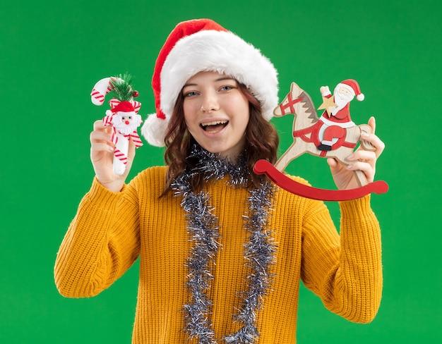 Fröhliches junges slawisches mädchen mit weihnachtsmütze und mit girlande um den hals, die zuckerstange und weihnachtsmann auf schaukelpferddekoration isoliert auf grüner wand mit kopierraum hält
